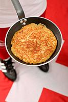 Footballer on Swiss flag holding frying pan with rösti