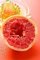Squeezed pink grapefruit in front of citrus squeezer