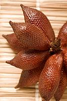 Several salak fruits on straw mat close_up
