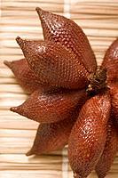 Several salak fruits on straw mat close_up