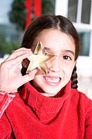 Girl holding cut_out biscuit in front of her eye