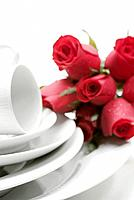 red roses and white porcelain dish on table