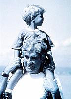 a man carrying his grandson on back