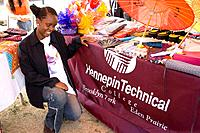 African American student shows banner of Hennepin Technical College  Dragon Festival Lake Phalen Park St Paul Minnesota USA