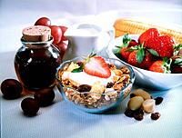 a bowl of cereal grains and some fruits on the table