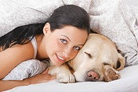 young woman and Labrador Retriever in bed