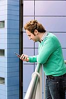 Man text messaging on balcony side view