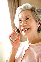 Senior woman smiling and using mobile phone