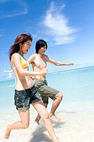 Young couple running on beach, smiling, Saipan