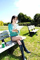 Young Woman Sketching on Bench, Side View,