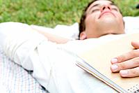 College Boy Lying on Grass with Holding Book