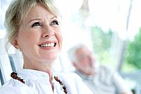 Senior couple sitting on rocking chair in terrace, smiling, differential focus