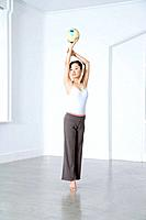 Woman practicing rhythmic gymnast performing with ball