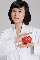 Young doctor holding heart shape on palm, portrait