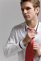 Businessman adjusting tie, close_up