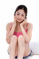 Young woman wearing headphones, listening to music