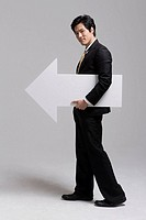 Businessman holding white arrow sign, portrait