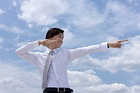 Businessman gesturing, cloudy sky in background, pointing