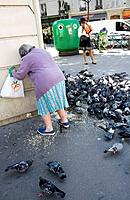 Old woman feeding pigeons, Paris, France
