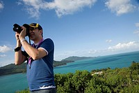 Tilted angle view of mountain range and ocean being photographed by man, Australia