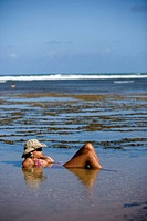 Woman lying partially submerged in rockpool, Praia do Forte, Bahia, Brazil