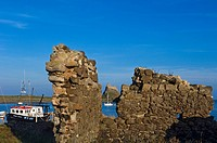 Lindesfarne Castle seen through breach in stone wall, Holy Island,Northumberland,UK