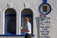 Tourists walking past a fish and chip shop in Broadstairs , Kent, England, United Kingdom