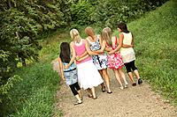 Rear view of girl friends walking on a path