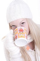 young woman in white winter clothes with cup of tea