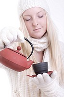 young woman in white winter clothes pouring tea from teapot into tea cup