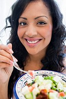 Woman holding bowl of salad and smiling high key/selective focus