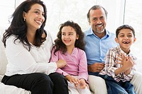 Grandparents sitting in living room with grandchildren smiling high key