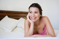 Woman relaxing on bed in bedroom smiling selective focus