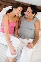 Couple relaxing on bed in bedroom smiling selective focus