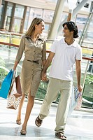 Couple walking in mall holding hands and smiling selective focus