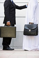 Two businessmen standing outdoors with briefcases