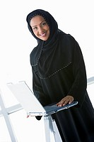 Woman indoors standing with laptop and smiling high key/selective focus