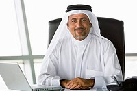 Businessman in office with laptop smiling high key/selective focus