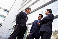 Three businessmen standing outdoors by building talking high key/selective focus