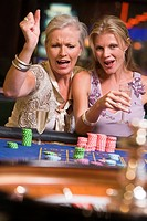 Two women in casino playing roulette and smiling selective focus