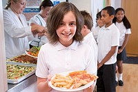 Students in cafeteria line with one holding unhealthy meal looking at camera depth of field
