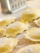 Uncooked Spinach and Ricotta Ravioli on a floured surface