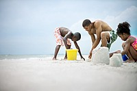 Kids Building Sand Castles with Dad on the Beach