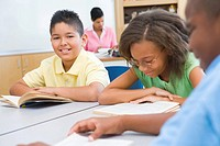 Students in class reading with teacher in background selective focus