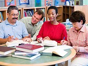Four people in library with books and notepads selective focus