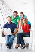Four people in lobby with laptop smiling
