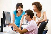 Three people in computer room pointing at monitor and smiling