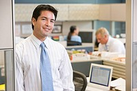 Businessman standing in cubicle smiling