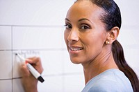 Businesswoman indoors writing on erasable board smiling