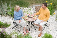 High angle view of a mid adult woman with a mature man having lunch in a garden
